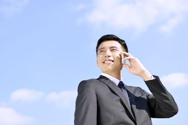 青空と電話をしているビジネスマン