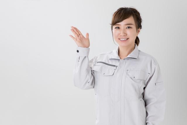 案内する作業着の女性スタッフ