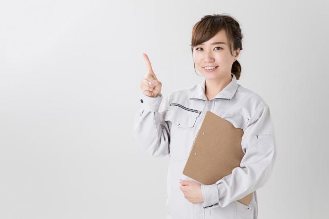 クリップボードを持った作業着の女性